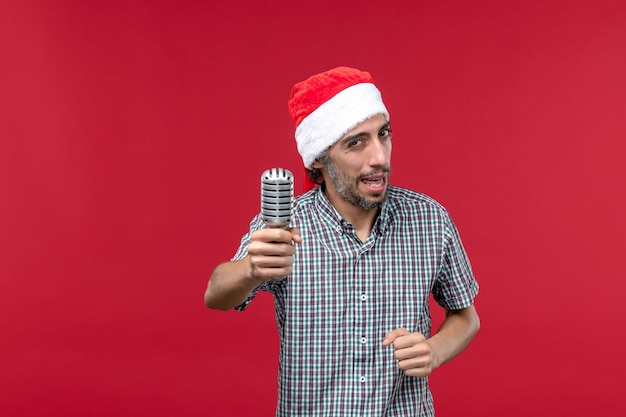 Front view young male holding mic and singing on a red background