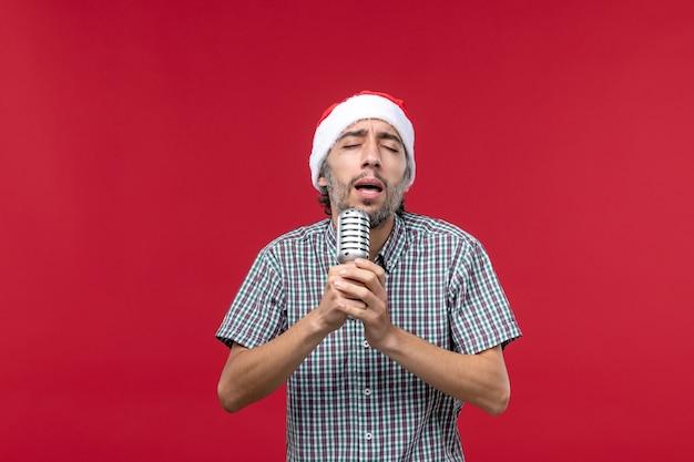 Vista frontale giovane maschio tenendo il microfono e cantando su sfondo rosso