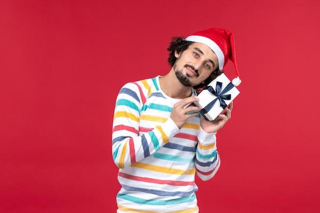 Вид спереди молодого мужчины, держащего новогодний подарок на красном столе, праздничная новогодняя эмоция