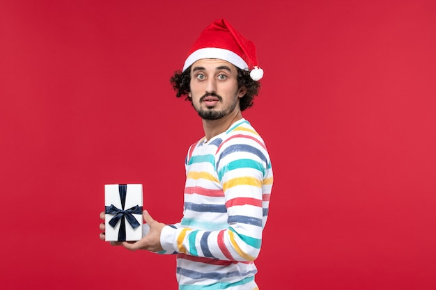 Вид спереди молодой мужчина держит новогодний подарок на красном фоне праздник новогодняя эмоция