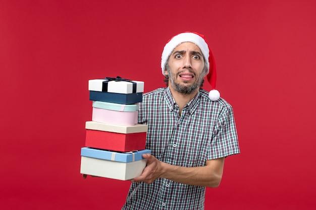 赤い背景に新年のプレゼントを保持している正面図若い男性