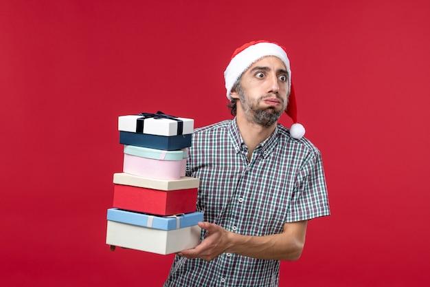 Giovane maschio di vista frontale che tiene i regali del nuovo anno sui precedenti rossi