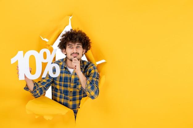 Вид спереди молодой мужчина держит на желтом фоне фото солнце распродажа эмоция цвет рубашка мужчина делает покупки