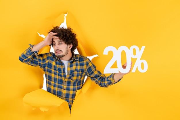 黄色の背景を保持している正面図若い男性