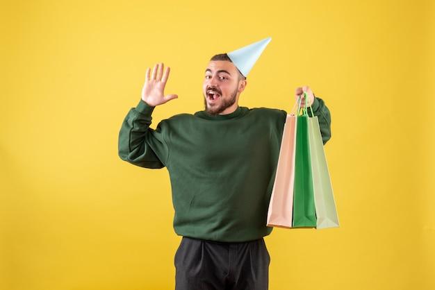 Вид спереди молодой мужчина держит пакеты с подарками на желтом фоне