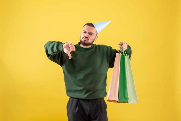 Вид спереди молодой мужчина держит пакеты с подарками на желтом фоне Бесплатные Фотографии