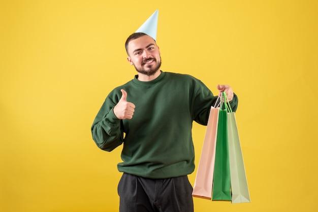黄色の背景にプレゼントとパッケージを保持している若い男性の正面図