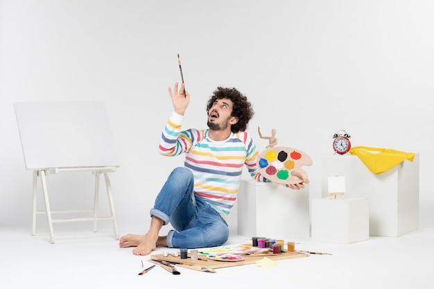 Vista frontale del giovane maschio che tiene le pitture e la nappa per disegnare sul muro bianco