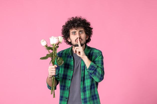 Vista frontale giovane maschio che tiene rose rosa su colore rosa