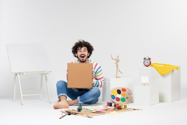 Front view of young male holding pizza box on white wall
