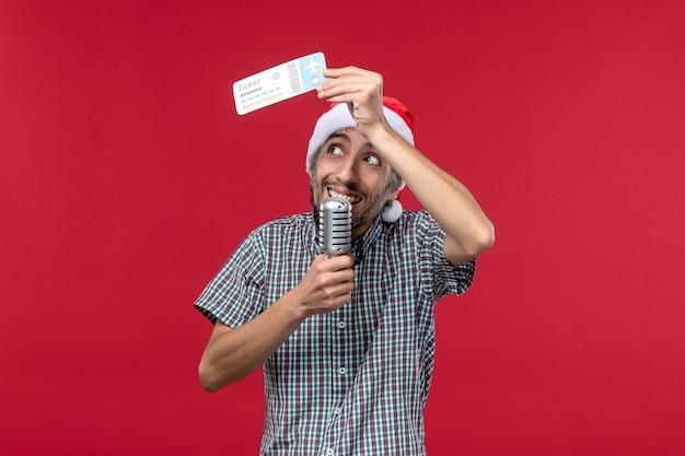 Вид спереди молодой мужчина держит билет на самолет и микрофон на красном фоне