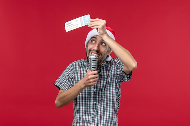 Front view young male holding plane ticket and mic on a red background