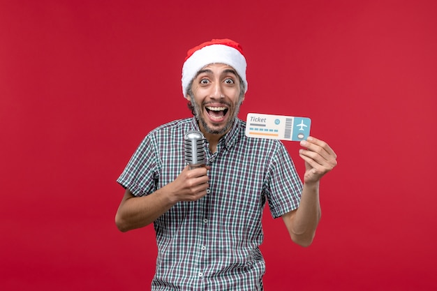 Front view young male holding plane ticket and mic on red background