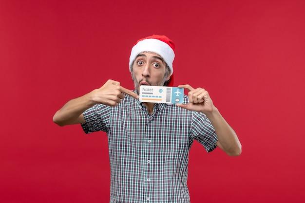 빨간색 배경에 비행기 티켓을 들고 전면보기 젊은 남성