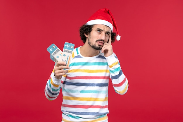 赤い背景の休日新年赤い飛行機で飛行機のチケットを保持している若い男性の正面図