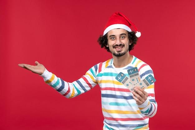赤い背景の飛行機の赤い飛行新年に飛行機のチケットを保持している正面図若い男性