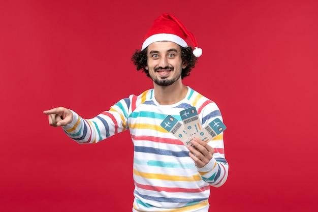 赤い背景の飛行機の赤い休日の新年に飛行機のチケットを保持している正面図若い男性