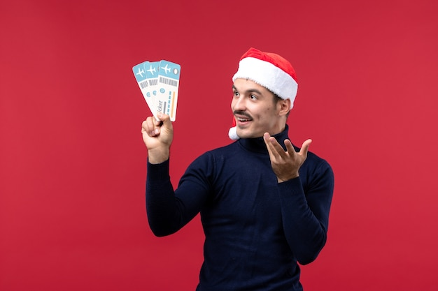 赤い背景に飛行機のチケットを保持している正面図若い男性