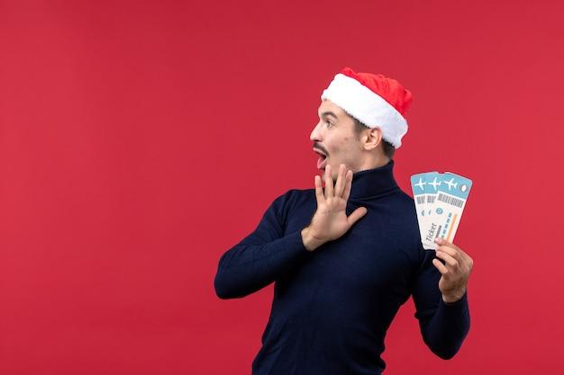 Вид спереди молодой мужчина держит билеты на самолет на красном фоне