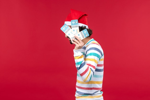 Front view young male holding plane tickets on red background plane flight new year red