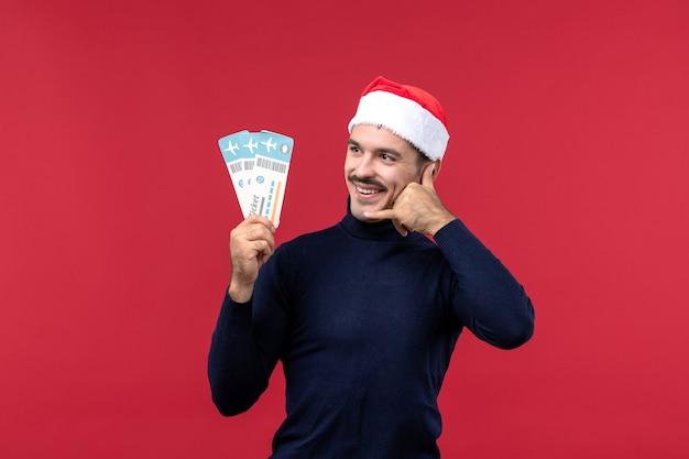 Vista frontale giovane maschio in possesso di biglietti aerei su sfondo rosso