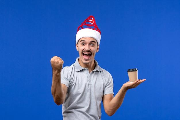 Vista frontale giovane maschio che tiene tazza di caffè di plastica sul nuovo anno maschio di emozione della parete blu