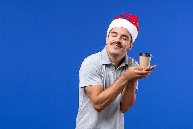Vista frontale giovane maschio che tiene tazza di caffè di plastica sulla parete blu emozioni maschio nuovo anno