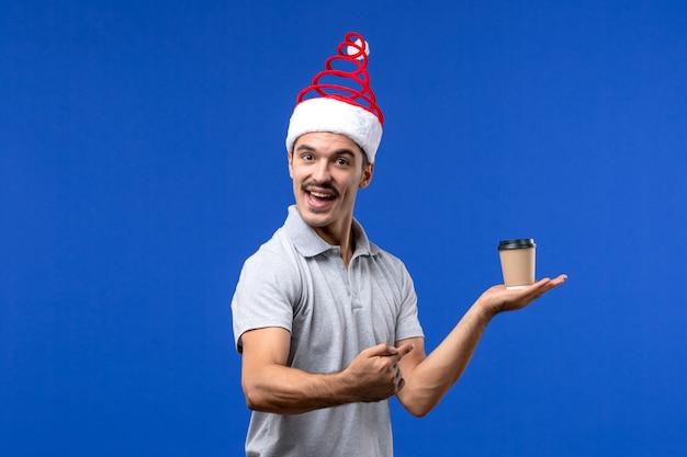 Vista frontale giovane maschio che tiene tazza di caffè di plastica sul nuovo anno maschio di festa della parete blu