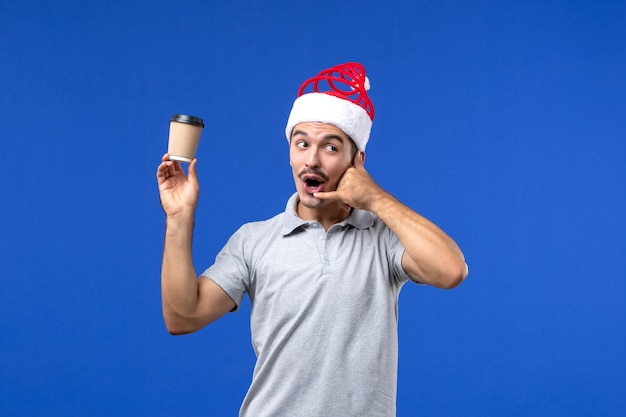 Vista frontale giovane maschio che tiene tazza di caffè di plastica sulla vacanza maschio del nuovo anno della parete blu