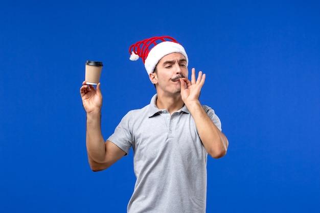 Vista frontale giovane maschio che tiene tazza di caffè di plastica sulla parete blu vacanze di capodanno maschio