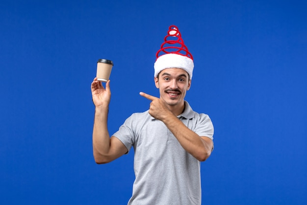 Vista frontale giovane maschio che tiene tazza di caffè di plastica sulla parete blu vacanze maschili di capodanno