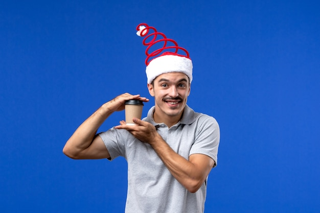 Front view young male holding plastic coffee cup on blue wall new year male holidays
