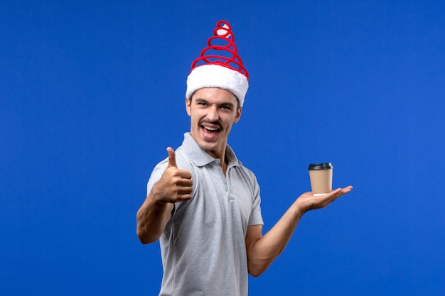 Вид спереди молодого мужчины, держащего пластиковую кофейную чашку на синем столе, праздник мужского нового года