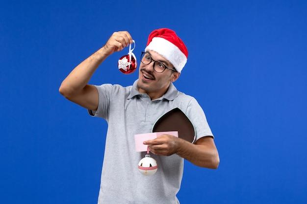 Vista frontale il giovane maschio che tiene i giocattoli di plastica dell'albero sulla vacanza umana del nuovo anno del fondo blu