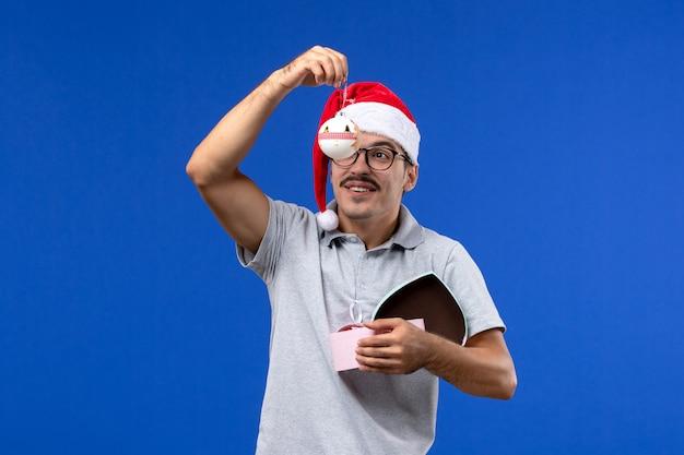 파란색 배경 인간의 새 해 휴일에 플라스틱 나무 장난감을 들고 전면보기 젊은 남성