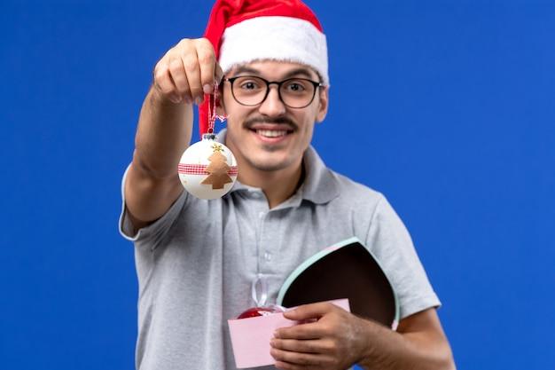 Вид спереди молодой мужчина держит пластиковые елочные игрушки на синем фоне людей новогодний праздник