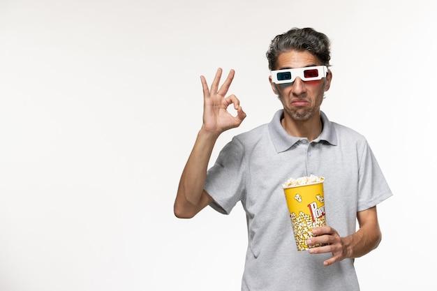 明るい白い表面にdサングラスでポップコーンを保持している正面図若い男性