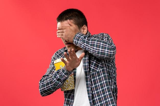 팝콘 패키지를 들고 밝은 붉은 벽 시네마 영화 극장 영화 남성에 그의 얼굴을 덮고 전면보기 젊은 남성