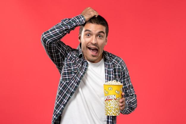 ポップコーンパッケージを保持し、明るい赤の壁の映画館の劇場映画映画でポーズをとる正面図若い男性
