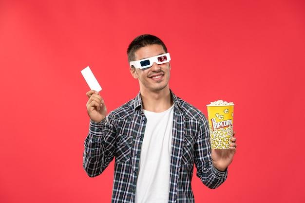 ポップコーンパッケージと明るい赤の壁の映画館映画館映画館の映画の男性のチケットを保持している正面図若い男性