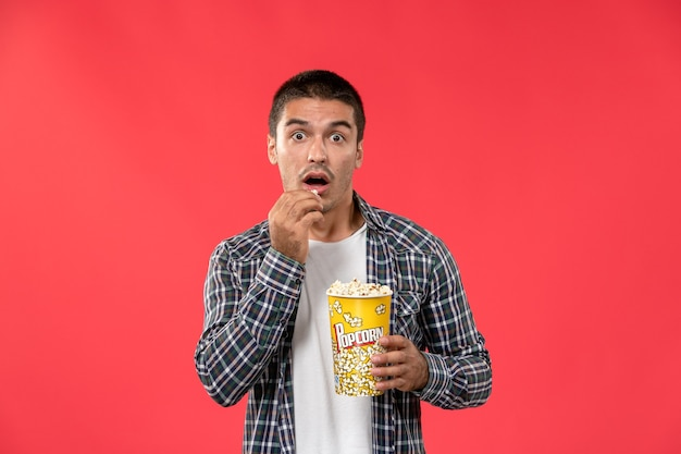 Front view young male holding popcorn package and eating on light red wall cinema theater film male movie