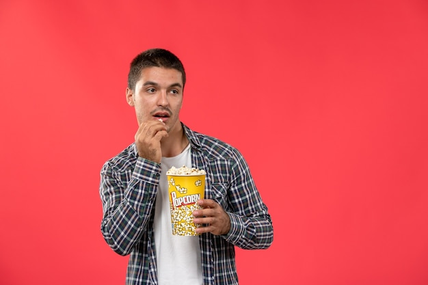 Front view young male holding popcorn package and eating on light red wall cinema theater film movie