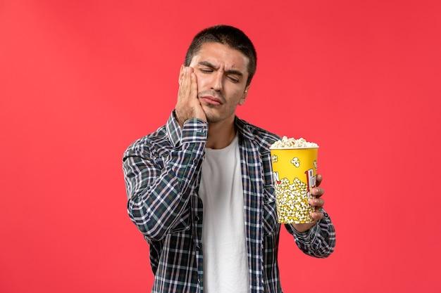 Vista frontale giovane maschio che tiene il pacchetto del popcorn che ha mal di denti sul film maschio del film del cinema del cinema della parete rosso-chiaro