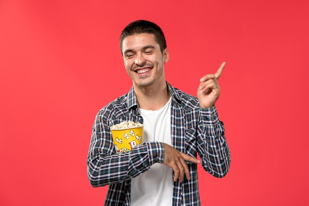 Front view young male holding popcorn package and laughing on red surface cinema theater film movie