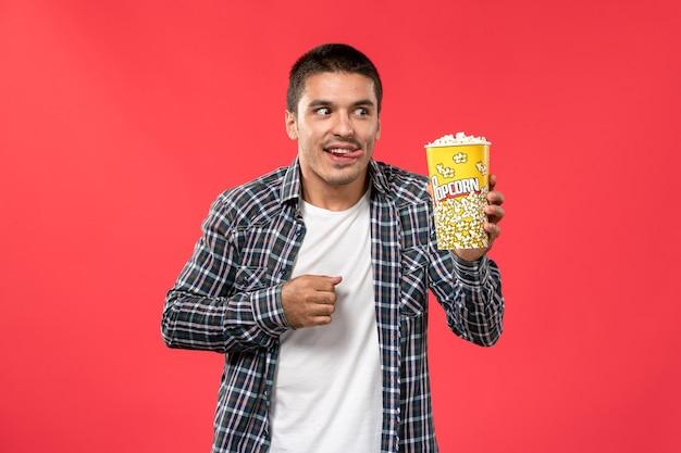 Вид спереди молодой мужчина с пакетом попкорна на светло-красной стене кинотеатр, кино