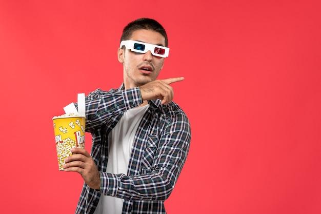Вид спереди молодой мужчина держит пакет попкорна на светло-красной стене мужской кинотеатр кинотеатр фильм веселые времена