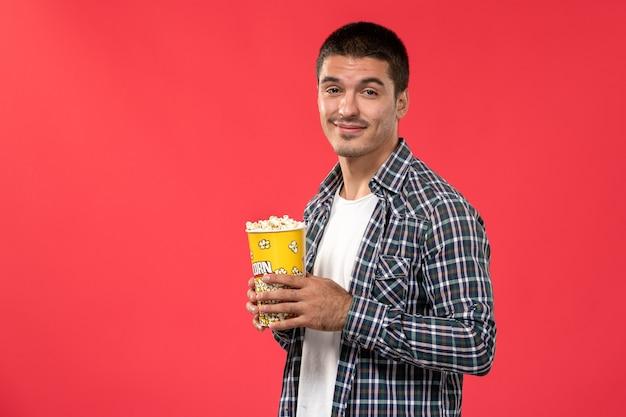 赤い表面の映画館の映画館の映画映画でポップコーンパッケージを保持している正面図若い男性