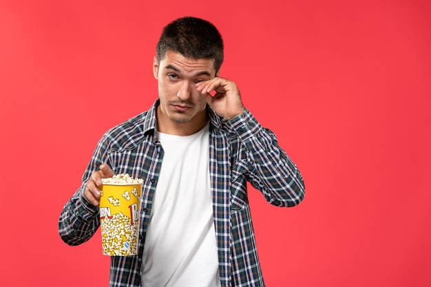 Front view young male holding popcorn package and rubbing his eyes on red surface cinema theater film movie