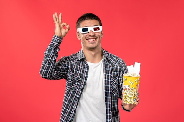 Front view young male holding popcorn package and tickets on red surface cinema theater film movie