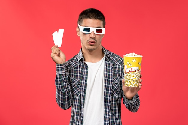 Front view young male holding popcorn package with tickets on the light-red wall male movies theater cinema film